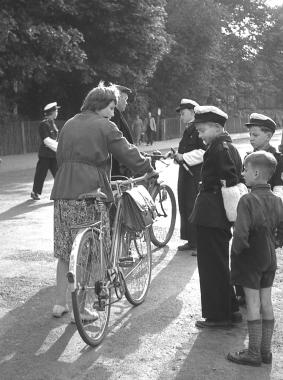 """Junge Pioniere der Arbeitsgemeinschaft """"Junge Verkehrshelfer"""" kontrollieren in der Friedrichstraße das verkehrsgerechte Verhalten und den Zustand der Fahrräder. - Dieter Oemler"""